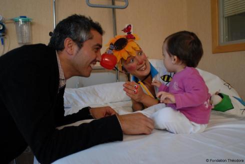 Imagen de uno de los Doctores Sonrisa acompañando a un niño feliz, por los pasillos de un hospita
