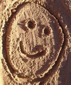 Sonrisa dibujada en la arena